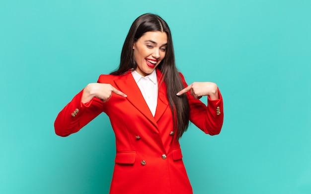 Młoda ładna kobieta czująca się szczęśliwa, zdziwiona i dumna, wskazująca na siebie z podekscytowanym, zdumionym spojrzeniem. pomysł na biznes