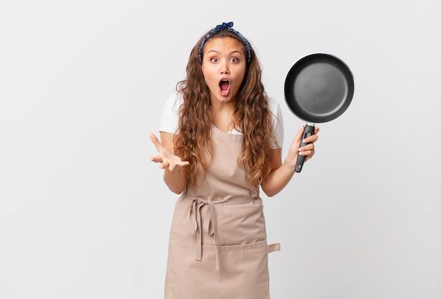 Młoda ładna kobieta czuje się bardzo zszokowana i zaskoczona koncepcją szefa kuchni i trzyma patelnię