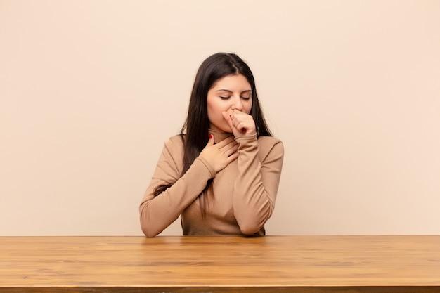 Młoda ładna kobieta czuje się chora z bólem gardła i objawami grypy, kaszel z usta pokryte siedzi przy stole