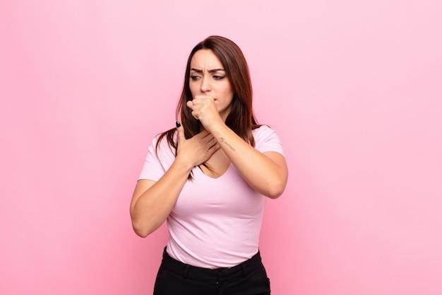 Młoda ładna kobieta czuje się chora z bólem gardła i objawami grypy, kaszel z ustami pokrytymi różową ścianą