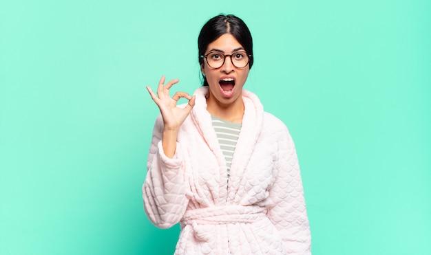 Młoda ładna kobieta czuje się dobrze i jest zadowolona, uśmiechając się z szeroko otwartymi ustami, robiąc ręką znak porządku. koncepcja piżamy