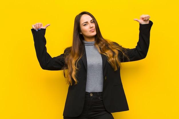 Młoda ładna kobieta czuje się dumna, arogancka i pewna siebie, wyglądająca na zadowoloną i udaną, wskazując na pracę własną lub koncepcję biznesową