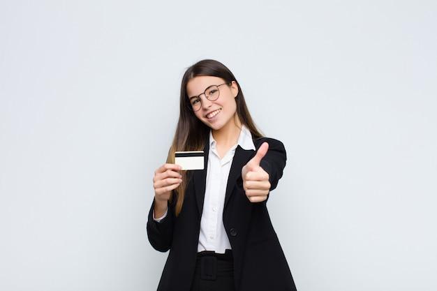 Młoda ładna kobieta czuje się dumna, beztroska, pewna siebie i szczęśliwa, uśmiecha się pozytywnie z kciukami w górę do karty kredytowej