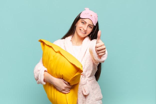 Młoda ładna kobieta czuje się dumna, beztroska, pewna siebie i szczęśliwa, uśmiechając się pozytywnie z kciukami do góry. budząc koncepcję piżamy