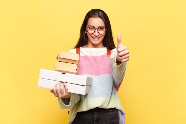 Młoda ładna kobieta czuje się dumna, beztroska, pewna siebie i szczęśliwa, uśmiechając się pozytywnie z kciukami do góry. weź koncepcję fast foodów aeay
