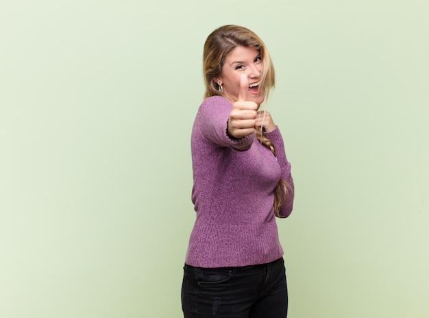 Młoda ładna kobieta czuje się dumna, beztroska, pewna siebie i szczęśliwa, uśmiechając się pozytywnie z kciukami do góry