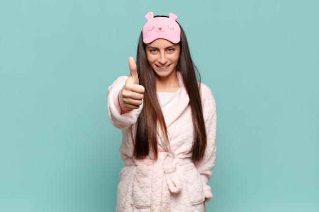 Młoda ładna kobieta czuje się dumna, beztroska, pewna siebie i szczęśliwa, uśmiechając się pozytywnie z kciukami w górę
