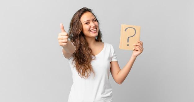 Młoda ładna kobieta czuje się dumna, uśmiecha się pozytywnie z kciukami do góry i trzyma znak zapytania