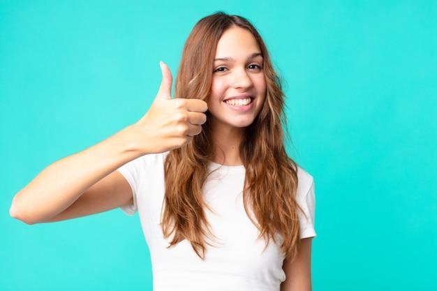 Młoda ładna kobieta czuje się dumna, uśmiecha się pozytywnie z kciukami w górę