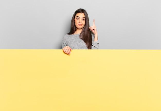 Młoda ładna kobieta czuje się jak geniusz trzymający dumnie palec w powietrzu po tym, jak zdała sobie sprawę ze świetnego pomysłu, mówiąc: eureka