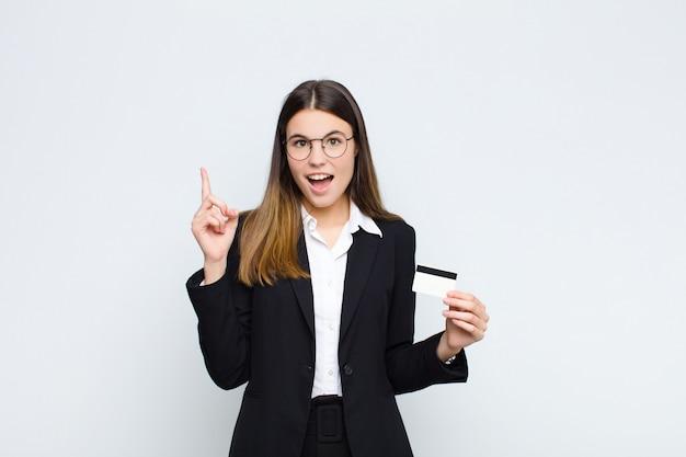 Młoda ładna kobieta czuje się jak szczęśliwa i podekscytowana geniusz po zrealizowaniu pomysłu, radośnie podnosząca palec, eureka! kartą kredytową