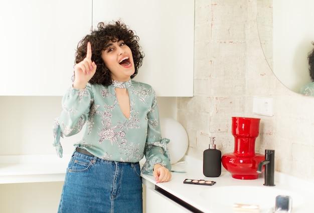 Młoda ładna kobieta czuje się jak szczęśliwa i podekscytowana geniusz po zrealizowaniu pomysłu, radośnie podnosząca palec, eureka!