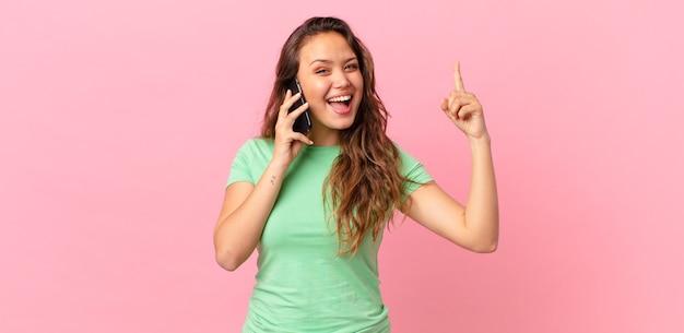 Młoda ładna kobieta czuje się jak szczęśliwy i podekscytowany geniusz po zrealizowaniu pomysłu i trzymaniu smartfona