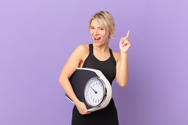 Młoda ładna kobieta czuje się jak szczęśliwy i podekscytowany geniusz po zrealizowaniu pomysłu. koncepcja diety