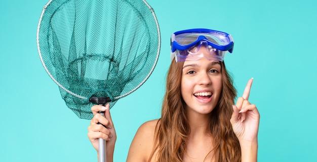 Młoda ładna kobieta czuje się jak szczęśliwy i podekscytowany geniusz po zrealizowaniu pomysłu z goglami i siecią rybacką