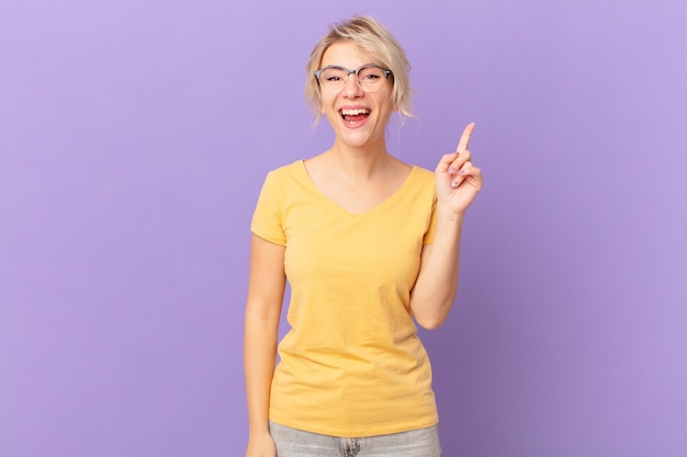 Młoda ładna kobieta czuje się jak szczęśliwy i podekscytowany geniusz po zrealizowaniu pomysłu