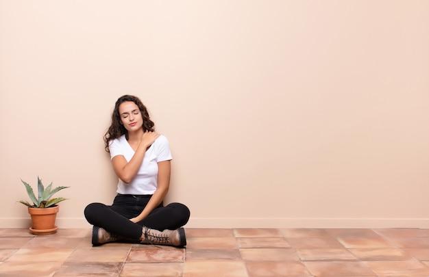 Młoda ładna kobieta czuje się niespokojna, chora, chora i nieszczęśliwa, cierpi na bolesny ból brzucha lub grypę siedzącą na tarasie