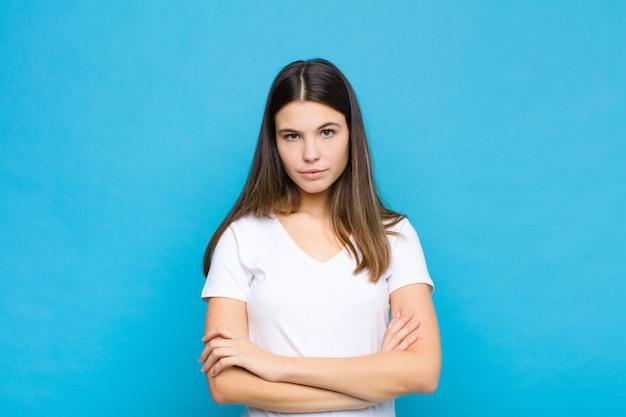 Młoda ładna kobieta czuje się niezadowolona i rozczarowana, wygląda na poważną, zirytowaną i wściekłą ze skrzyżowanymi rękami na niebieskiej ścianie