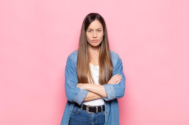 Młoda ładna kobieta czuje się niezadowolona i rozczarowana, wygląda poważnie, zirytowana i wściekła ze skrzyżowanymi rękami