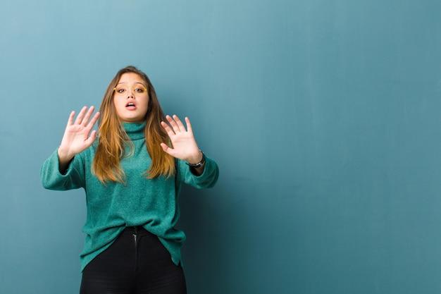 Młoda ładna kobieta czuje się oszołomiona i przestraszona, bojąca się czegoś przerażającego, z otwartymi rękami z przodu mówiąc: trzymaj się z dala