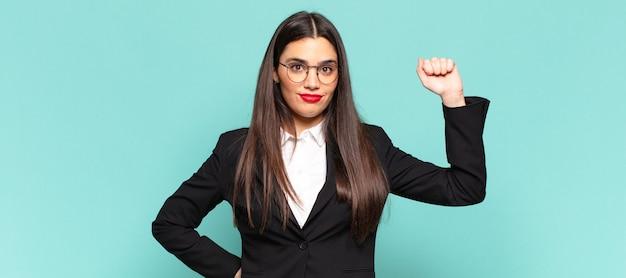 Młoda ładna kobieta czuje się poważna, silna i buntownicza, podnosi pięść, protestuje lub walczy o rewolucję. pomysł na biznes