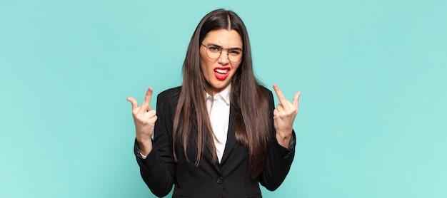 Młoda ładna kobieta czuje się prowokacyjna, agresywna i nieprzyzwoita, machając środkowym palcem, o buntowniczym nastawieniu