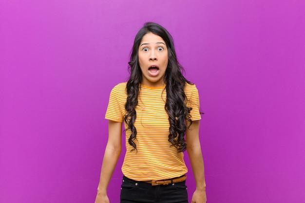 Młoda ładna kobieta czuje się przerażona i zszokowana, z szeroko otwartymi ustami z zaskoczenia na fioletowej ścianie