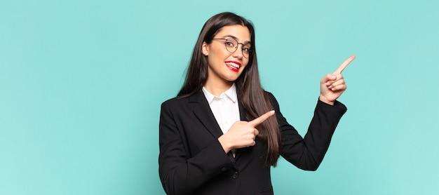 Młoda ładna kobieta czuje się radosna i zaskoczona, uśmiechając się z szokiem na twarzy i wskazując na bok. pomysł na biznes