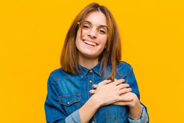Młoda ładna kobieta czuje się romantycznie, szczęśliwa i zakochana, uśmiecha się wesoło i trzyma ręce blisko serca na żółtej ścianie