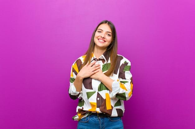 Młoda ładna kobieta czuje się romantycznie, szczęśliwa i zakochana, uśmiecha się wesoło i trzyma ręce blisko serca o ścianę fioletową