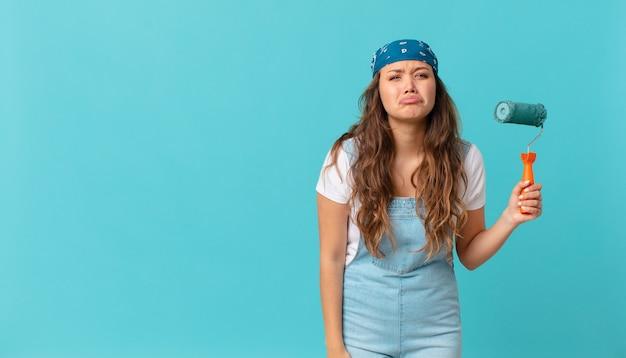 Młoda ładna kobieta czuje się smutna i jęczy z nieszczęśliwym spojrzeniem, płacze i maluje ścianę
