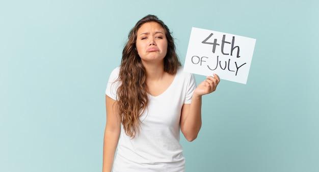 Młoda ładna kobieta czuje się smutna i marudna z nieszczęśliwym spojrzeniem i płaczącą koncepcją dnia niepodległości