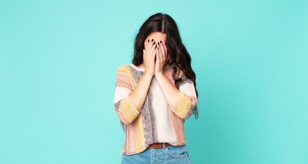 Młoda ładna kobieta czuje się smutna, sfrustrowana, zdenerwowana i przygnębiona, zakrywa twarz obiema rękami, płacze