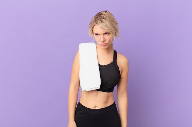 Młoda ładna kobieta czuje się smutna, zdenerwowana lub zła i patrzy w bok. koncepcja fitness
