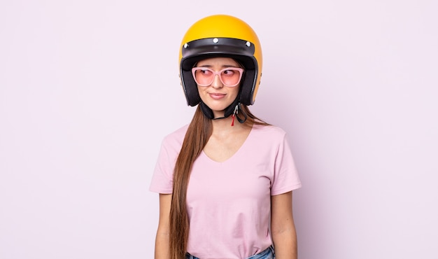 Młoda ładna kobieta czuje się smutna, zdenerwowana lub zła i patrzy w bok. motocyklista i kask