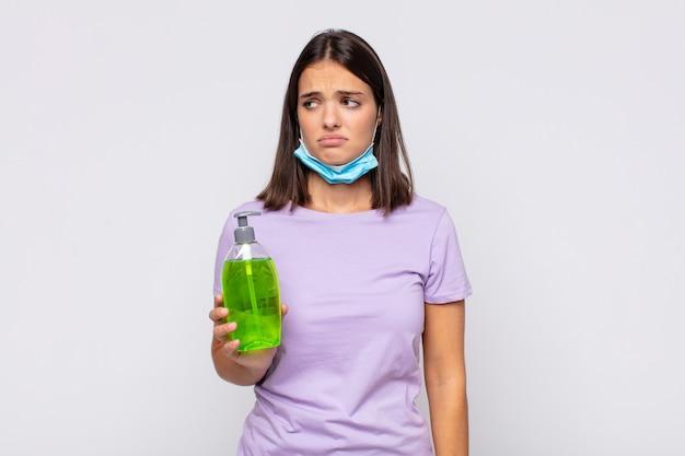 Młoda ładna kobieta czuje się smutna, zdenerwowana lub zła i patrzy w bok z negatywnym nastawieniem, marszcząc brwi w niezgodzie
