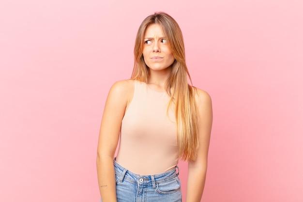 Młoda ładna kobieta czuje się smutna, zdenerwowana lub zła i patrzy w bok