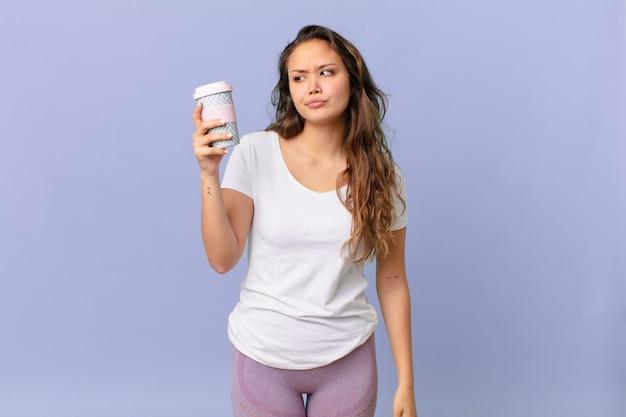 Młoda ładna kobieta czuje się smutna, zdenerwowana lub zła, patrzy w bok i trzyma kawę