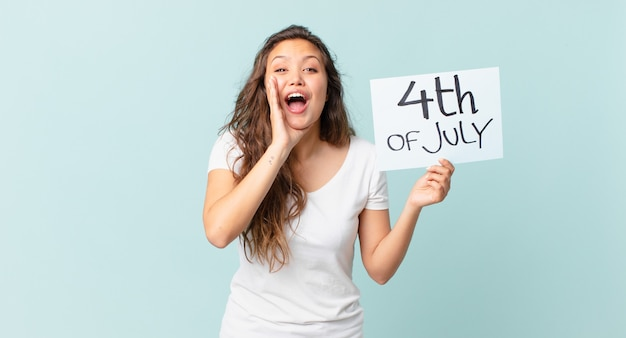 Młoda ładna kobieta czuje się szczęśliwa, dając wielki okrzyk z rękami obok koncepcji dnia niepodległości ust