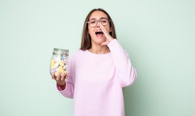 Młoda ładna kobieta czuje się szczęśliwa, dając wielki okrzyk z rękami przy ustach. koncepcja cukierków galaretkowych