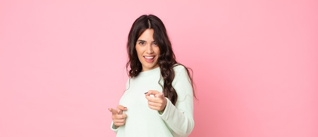 Młoda ładna kobieta czuje się szczęśliwa, fajna, zadowolona, zrelaksowana i odnosząca sukcesy, wskazując na aparat, wybierając ciebie
