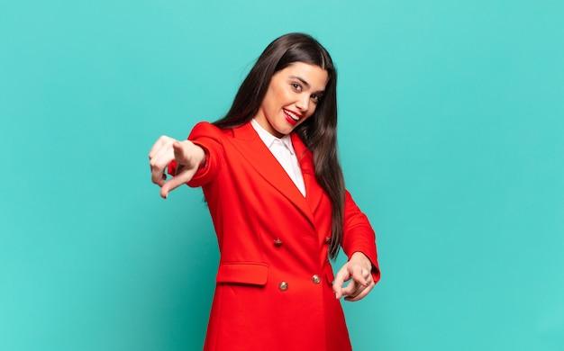 Młoda ładna kobieta czuje się szczęśliwa i pewna siebie, wskazując obiema rękami na aparat i śmiejąc się, wybierając ciebie. pomysł na biznes
