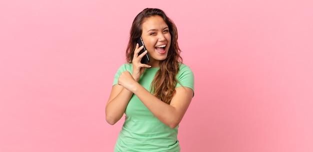 Młoda ładna kobieta czuje się szczęśliwa i staje przed wyzwaniem lub świętuje i trzyma smartfona