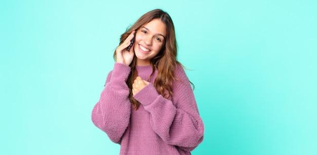 Młoda ładna kobieta czuje się szczęśliwa i staje przed wyzwaniem lub świętuje i używa smartfona
