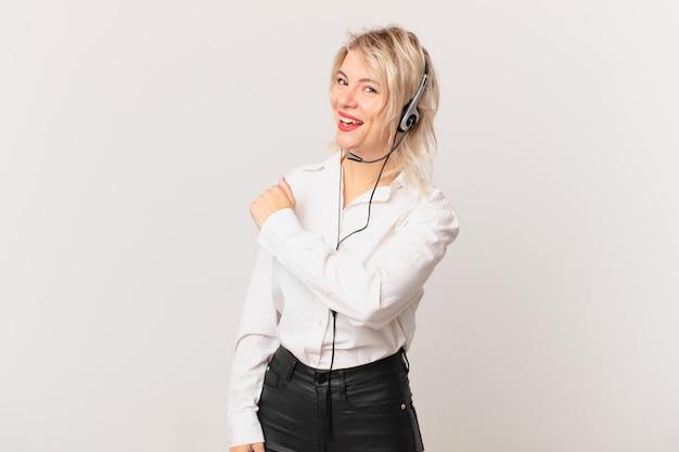 Młoda ładna kobieta czuje się szczęśliwa i stoi przed wyzwaniem lub świętuje. koncepcja telemarketingu