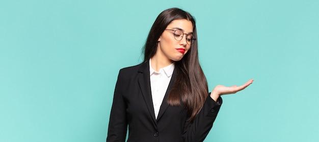 Młoda ładna kobieta czuje się szczęśliwa i uśmiecha się od niechcenia, patrząc na przedmiot lub koncepcję trzymaną na dłoni z boku. pomysł na biznes