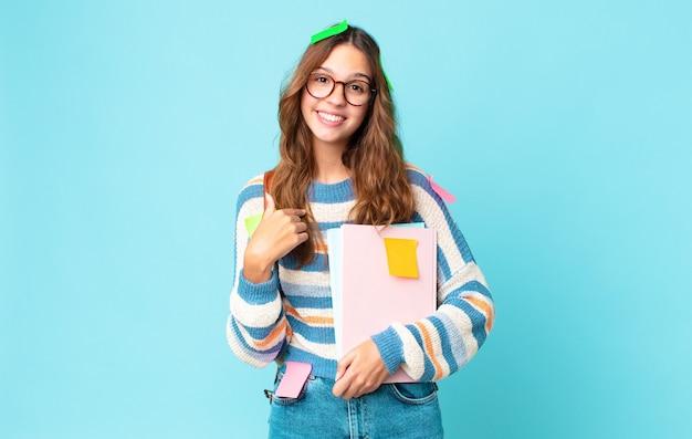 Młoda ładna kobieta czuje się szczęśliwa i wskazuje na siebie z podekscytowaną torbą i trzymając książki