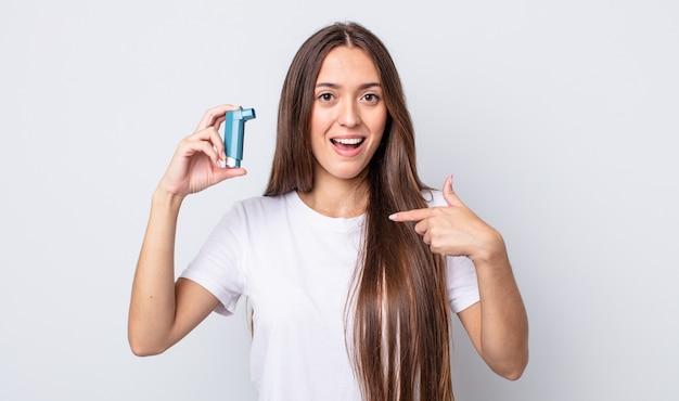 Młoda ładna kobieta czuje się szczęśliwa i wskazuje na siebie z podekscytowaniem. koncepcja astmy
