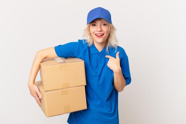Młoda ładna kobieta czuje się szczęśliwa i wskazuje na siebie z podekscytowaniem. koncepcja dostarczania paczek