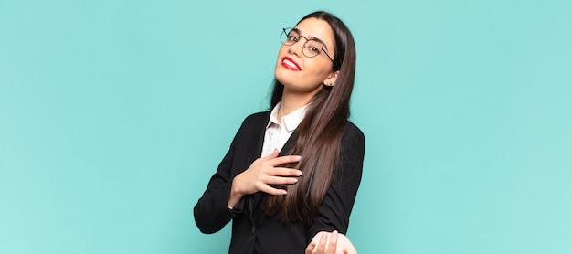 Młoda ładna kobieta czuje się szczęśliwa i zakochana, uśmiecha się z jedną ręką obok serca, a drugą wyciągniętą do przodu. pomysł na biznes